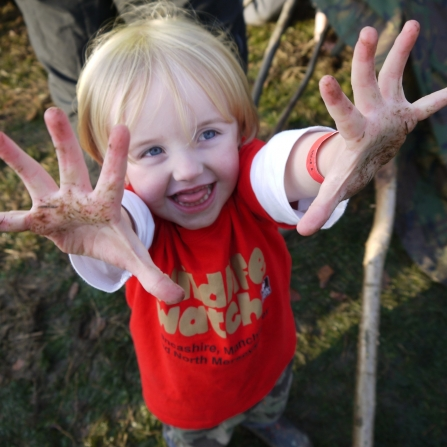 Child in Wildlife Watch t-shirt with muddy hands, Julie Norman